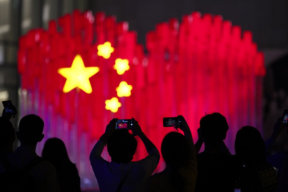 Visitors take photos with their smart phones of an installation depicting a heart shape Chinese national flag in Shanghai, China, Friday, Sept. 27, 2019. China will mark its 70th anniversary on Oct. 1, 2019.