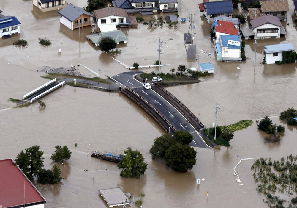 Cars are stranded on a road as the city is submerged in muddy waters after an embankment of the Chikuma River broke, in Nagano, central Japan, Sunday, Oct. 13, 2019.
