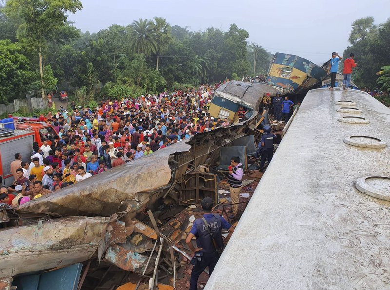 People gather near badly damages coaches after two speeding trains collided in in Brahmanbaria district, 82 kilometers (51 miles) east of the capital, Dhaka, Bangladesh, Tuesday, Nov.12, 2019.