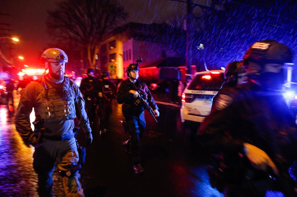 Law enforcement personnel walk near the scene following a shooting, Tuesday, Dec. 10, 2019, in Jersey City, N.J.