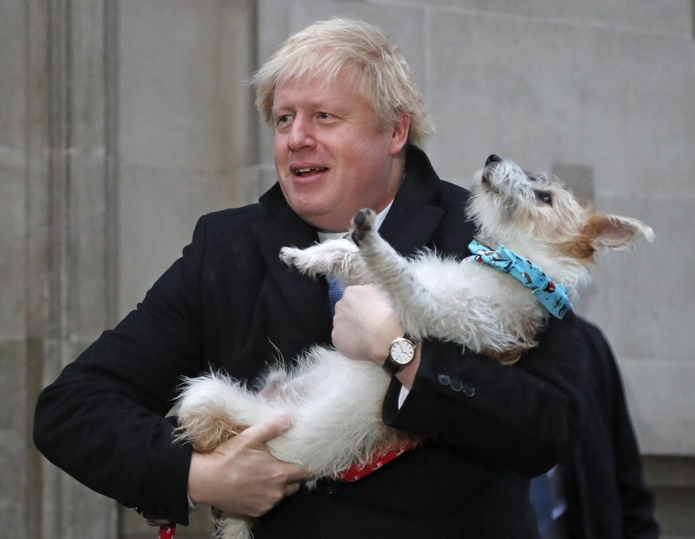 Britain's Prime Minister and Conservative Party leader Boris Johnson holds his dog Dilyn as he leaves after voting in the general election at Methodist Central Hall, Westminster, London, Thursday, Dec. 12, 2019.