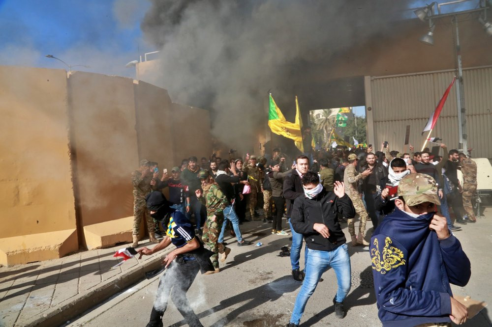 US soldiers fire tear gas towards protesters who broke into the U.S. embassy compound, in Baghdad, Iraq, Tuesday, Dec. 31, 2019.