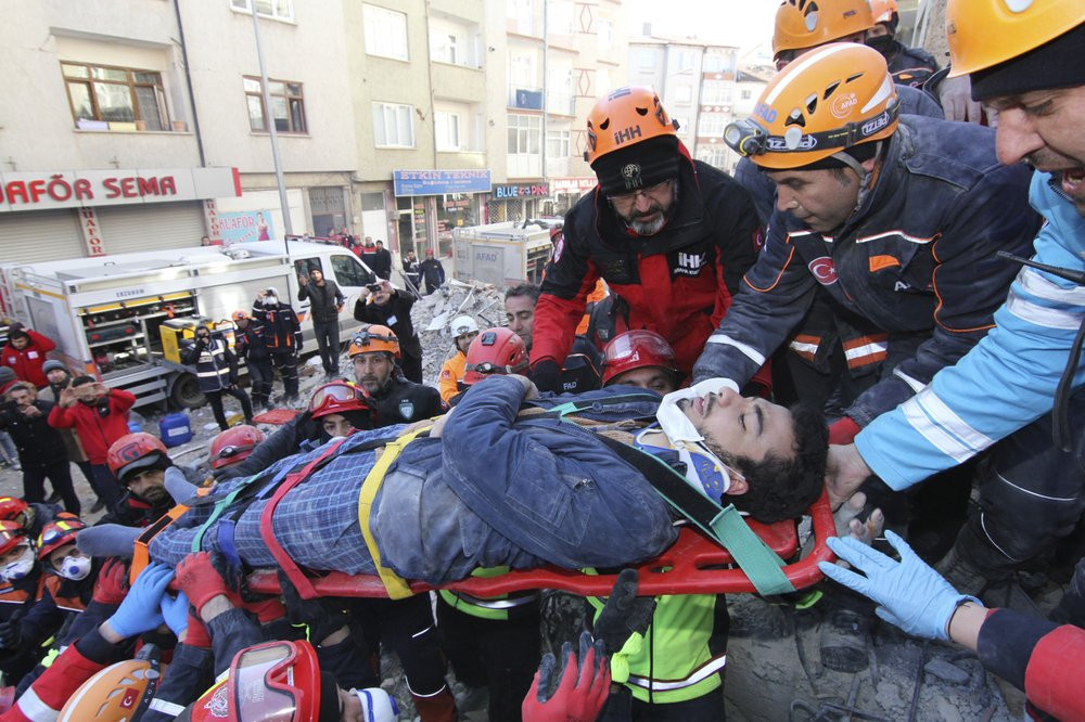 Rescue workers carry a wounded man that was found alive in the rubble of a building destroyed on Friday's earthquake in Elazig, eastern Turkey, Saturday, Jan. 25, 2020.