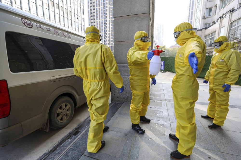 In this Jan. 30, 2020 file photo, funeral workers disinfect themselves after handling a virus victim in Wuhan in central China's Hubei Province, Thursday, Jan. 30, 2020.
