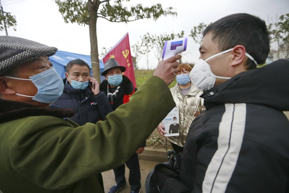 In this Saturday, Feb. 1, 2020, photo, a government worker takes the temperature of a passer-by at a checkpoint in Suining in southwestern China's Sichuan Province.