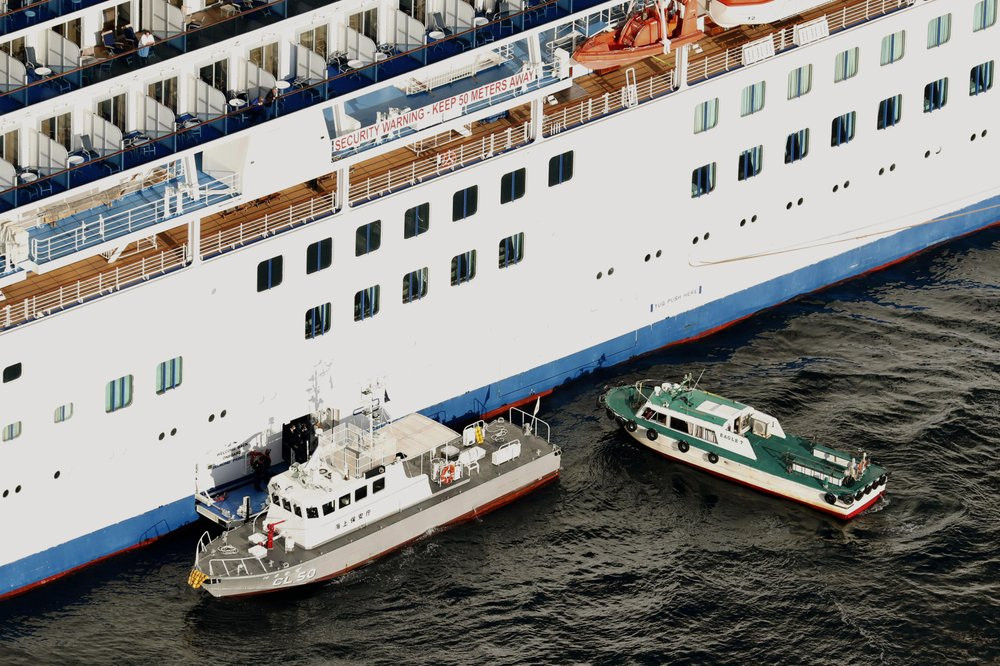 Japan Coast Guard's patrol boat, left, is brought alongside the cruise ship Diamond Princess to take passengers tested positive for coronavirus to hospitals off Yokohama, south of Tokyo, Wednesday, Feb. 5, 2020.