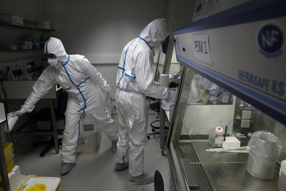 French lab scientists in hazmat gear inserting liquid in test tube manipulate potentially infected patient samples at Pasteur Institute in Paris, Thursday, Feb. 6, 2020.