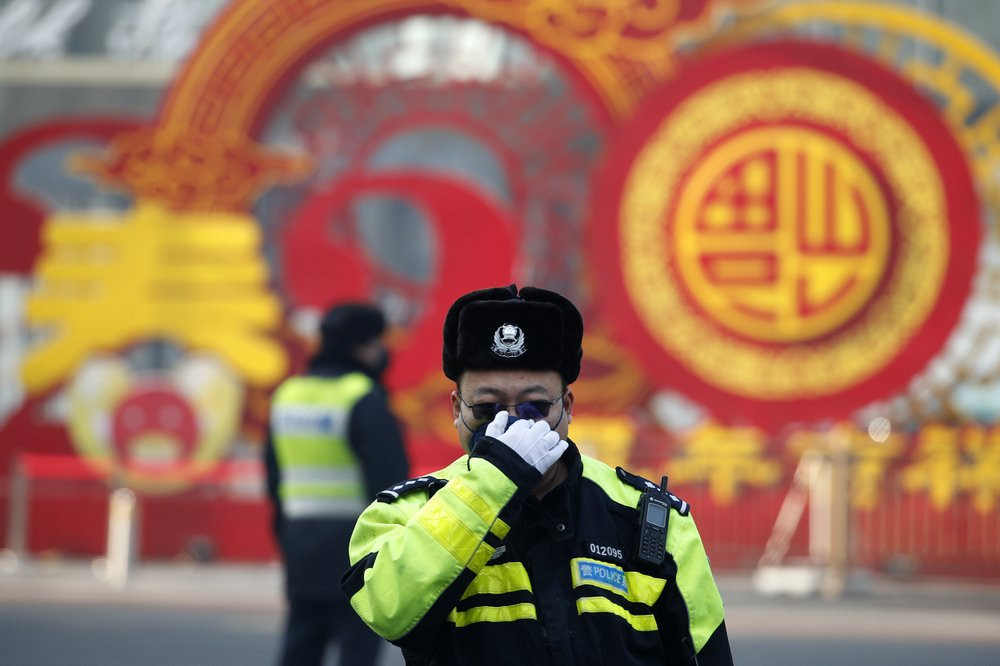 A traffic policeman adjusts his mask on a street in Beijing, Sunday, Feb. 9, 2020.