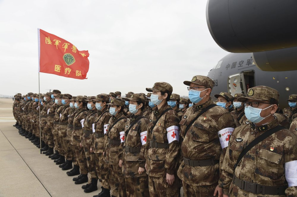 In this photo released by China's Xinhua News Agency, Chinese military medics arrive at the Tianhe International Airport in Wuhan, central China's Hubei Province, Feb. 13, 2020.
