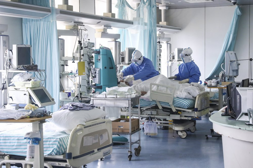 In this Feb. 13, 2020 photo released by China's Xinhua News Agency, nurses in protective suits treat a patient in the intensive care unit at Ditan Hospital in Beijing, one of the hospitals in China's capital that are receiving COVID-19 patients.