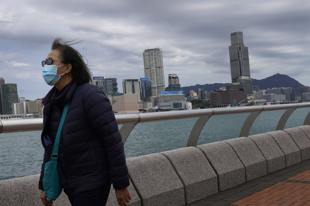 A woman wearing a face mask walks at the waterfront against the Victoria Habour in Hong Kong Sunday, Feb. 16, 2020. COVID-19 viral illness has sickened tens of thousands of people in China since December.