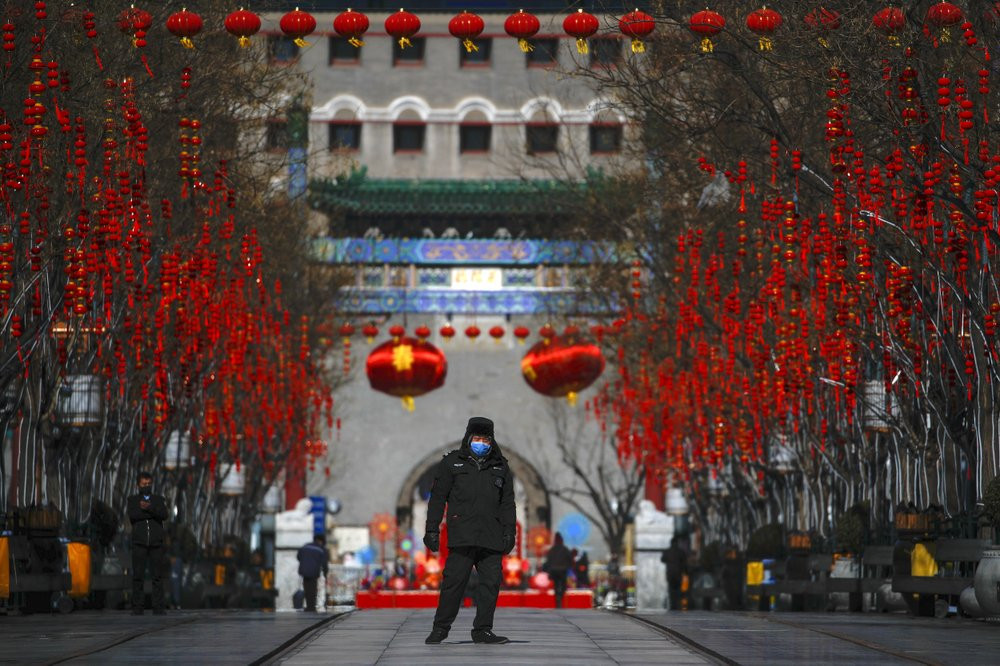 A security guard wearing a face mask walks through a quiet main Qianmen Street, a popular tourist spot, in Beijing, Sunday, Feb. 16, 2020.