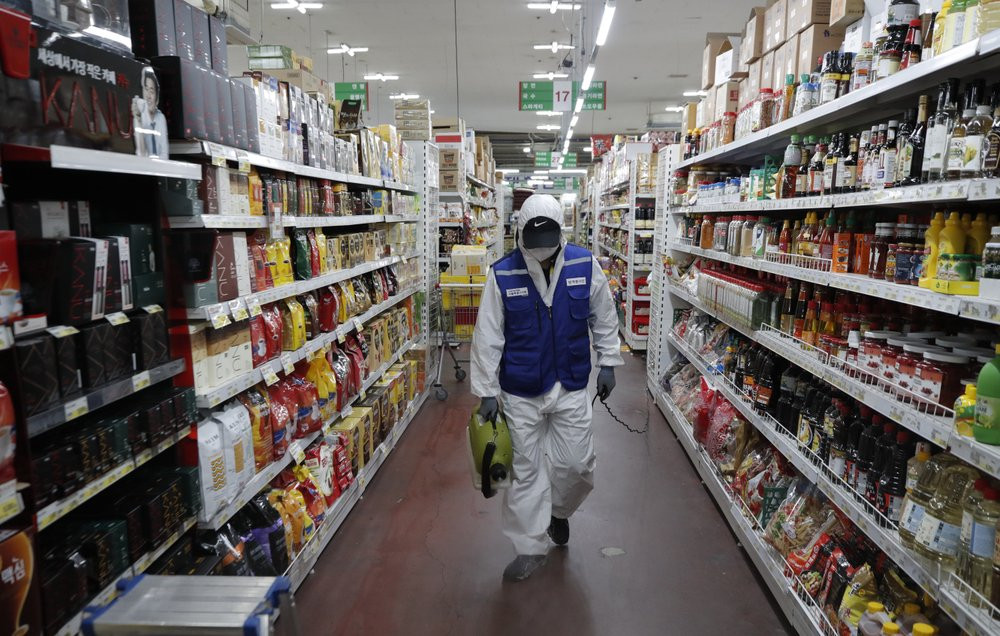 A worker wearing a protective suit sprays disinfectant as a precaution against the COVID-19 at a market in Seoul, South Korea, Thursday, Feb. 27, 2020.
