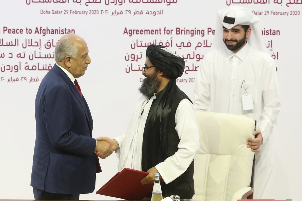 U.S. peace envoy Zalmay Khalilzad, left, and Mullah Abdul Ghani Baradar, the Taliban group's top political leader shack hands after signing a peace agreement between Taliban and U.S. officials in Doha, Qatar, Saturday, Feb. 29, 2020.
