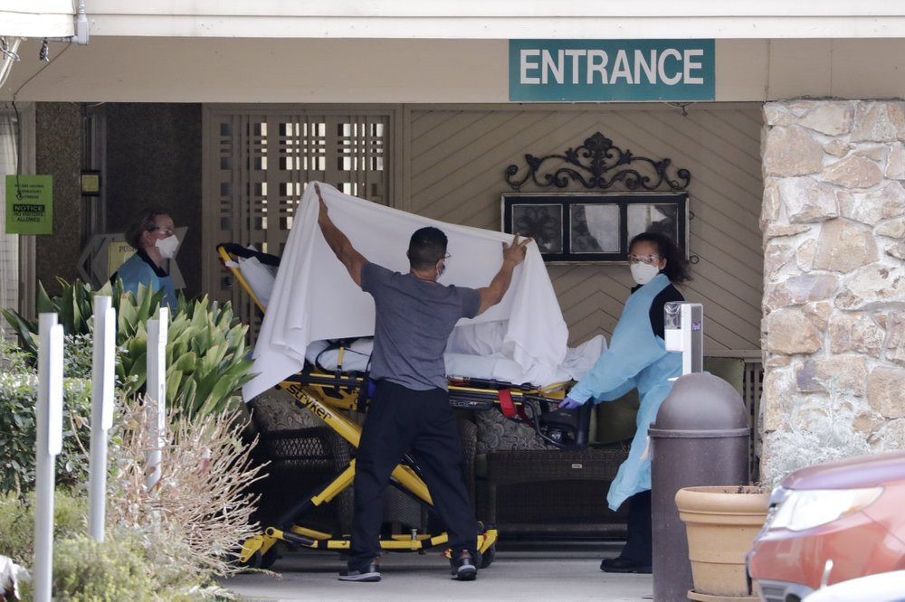A person is taken by stretcher to a waiting ambulance from a nursing facility where more than 50 people are sick and being tested for the COVID-19 virus, Saturday, Feb. 29, 2020, in Kirkland, Washington.