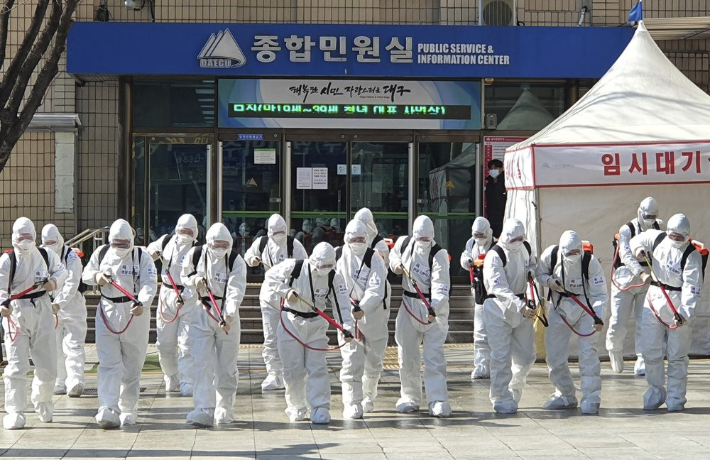 South Korean soldiers wearing protective suits spray disinfectant to prevent the spread of a new coronavirus in front of the Daegu city hall in Daegu, South Korea, Monday, March 2, 2020.