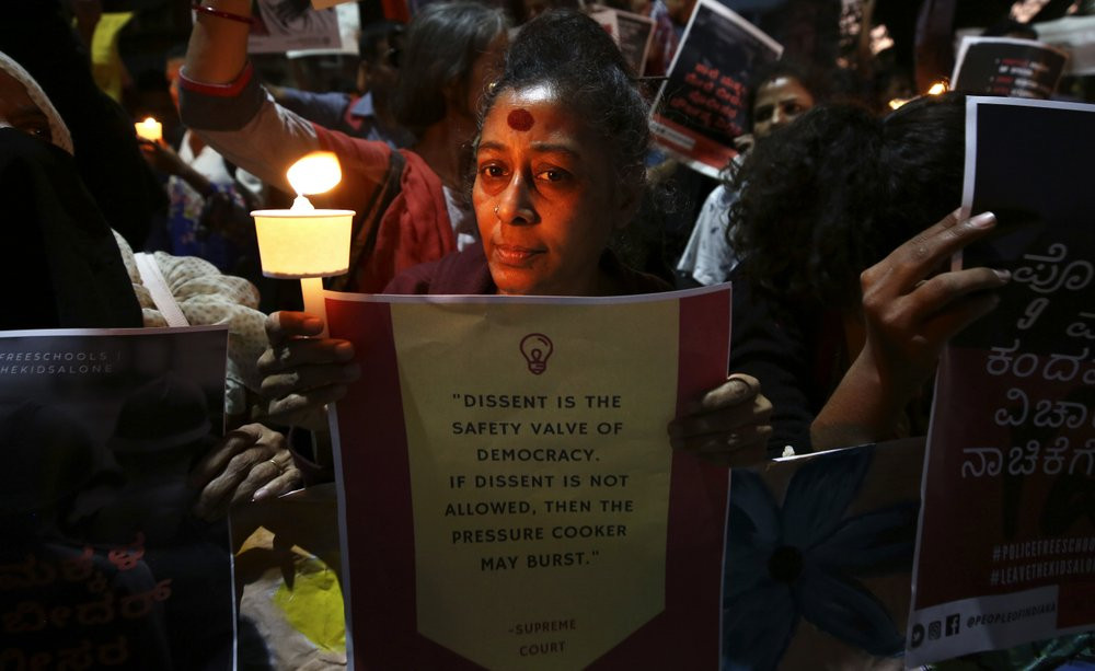 In this Tuesday, Feb. 4, 2020 photo, an Indian woman holds a candle and placard during a protest against the sedition case filed by police against a school after a play preformed by students denouncing a new citizenship law, in Bangalore, India.