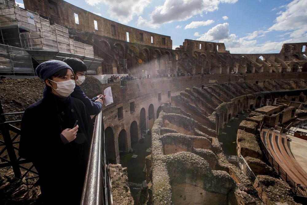 Tourists visit the Colosseum, in Rome, Saturday, March 7, 2020.