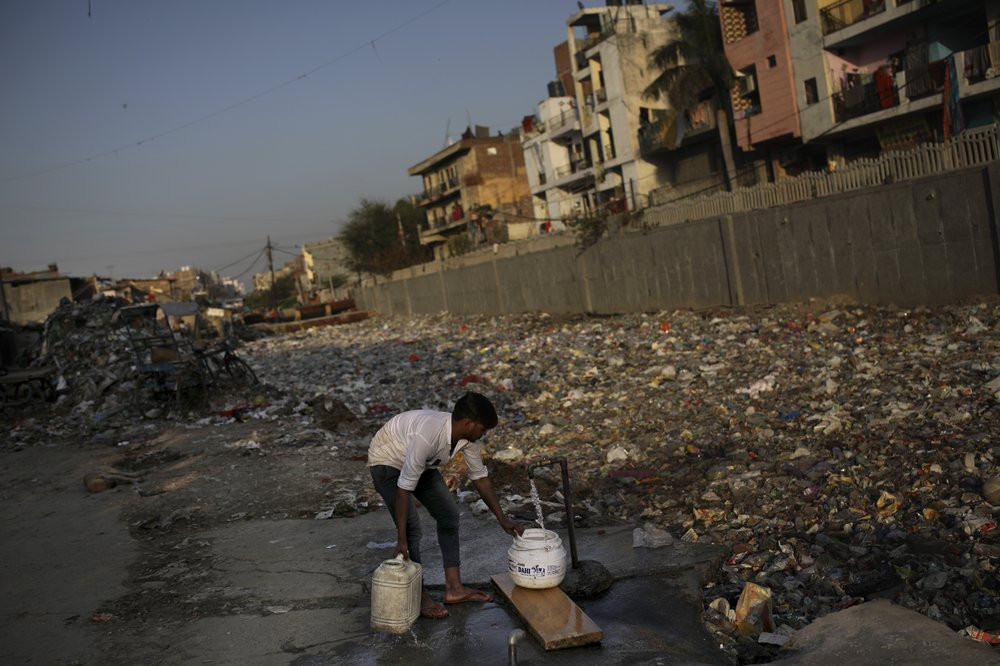 In this Tuesday, March 17, 2020 photo, a slum dweller fills water from a tap next to a drain filled with plastic and other filth in New Delhi, India.