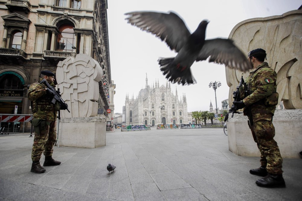 Italian soldiers patrol as the Duomo gothic cathedral is visible in background, in Milan, Friday, March 20, 2020.