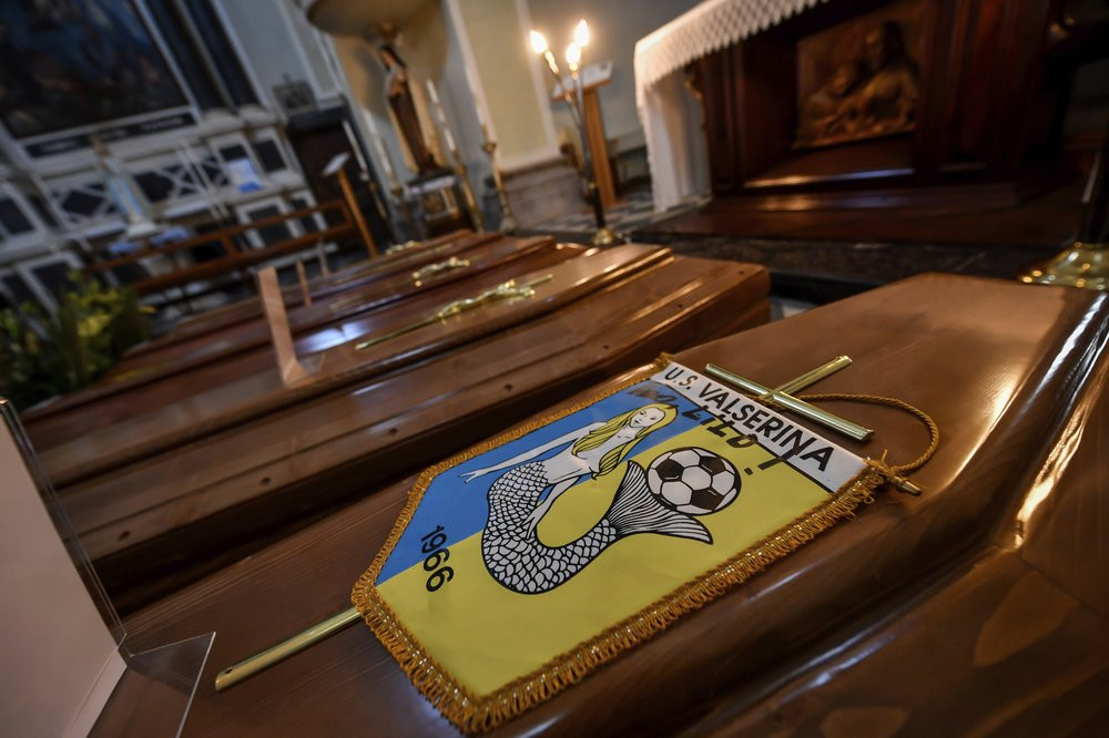 Coffins, one of them with the pennant of the local soccer team, wait to be transported to cemetery, in the church of Serina, near Bergamo, Northern Italy, Saturday, March 21, 2020.