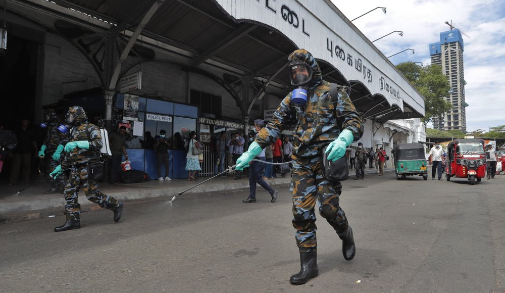 Sri Lankan government soldiers in protective clothes spray disinfectants at a railway station in Colombo, Sri Lanka, Wednesday, March 18, 2020.