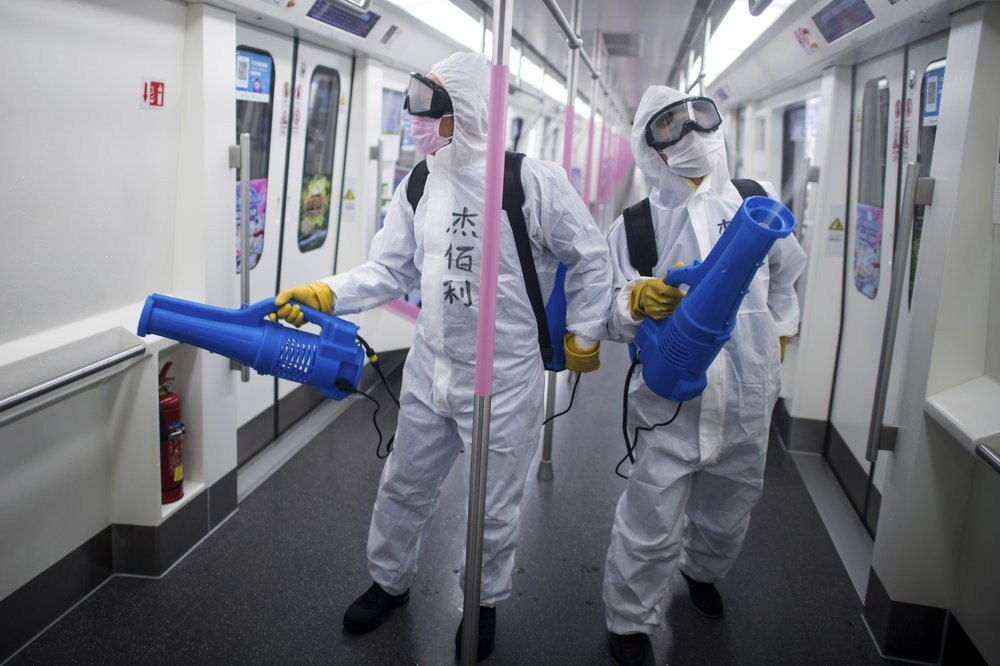 In this March 23, 2020 photo released by Xinhua News Agency, workers disinfect a subway train in preparation for the restoration of public transport in Wuhan, in central China's Hubei province.