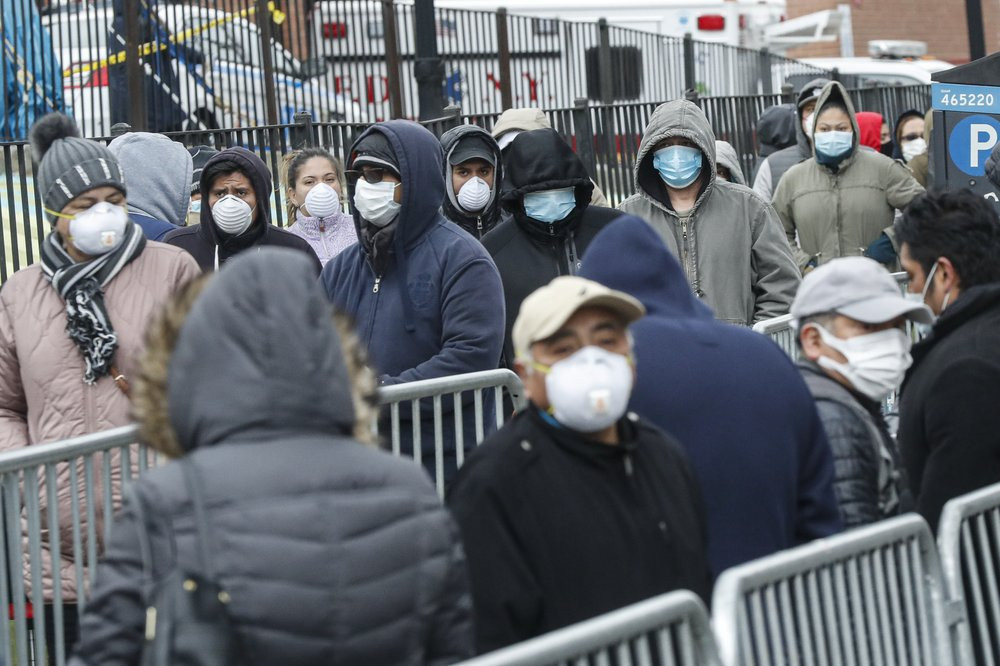 Patients wear personal protective equipment while maintaining social distancing as they wait in line for a COVID-19 test at Elmhurst Hospital Center, Wednesday, March 25, 2020, in New York.