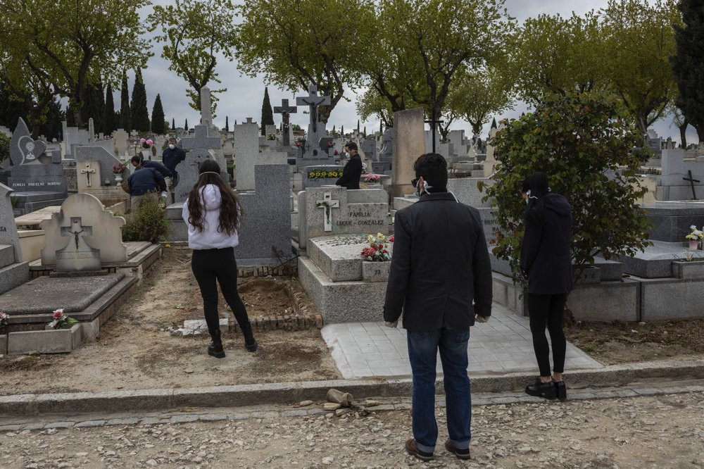 Relatives wearing face masks to protect against coronavirus, observe social distancing guidelines during a burial at a Madrid cemetery during the coronavirus outbreak in Madrid, Spain, Friday, March 27, 2020.