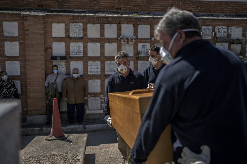 The daughter and husband, center left, no names available, of an elderly victim of the COVID-19 stand as undertakers place the coffin in the grave at the Almudena cemetery in Madrid, Spain, Saturday March 28, 2020.