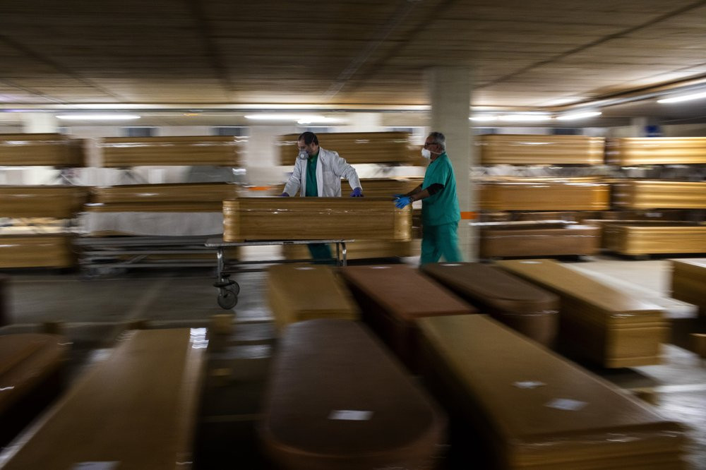 Workers move a coffin with the body of a victim of coronavirus as others coffins are stored waiting for burial or cremation at the Collserola morgue in Barcelona, Spain, Thursday, April 2, 2020.