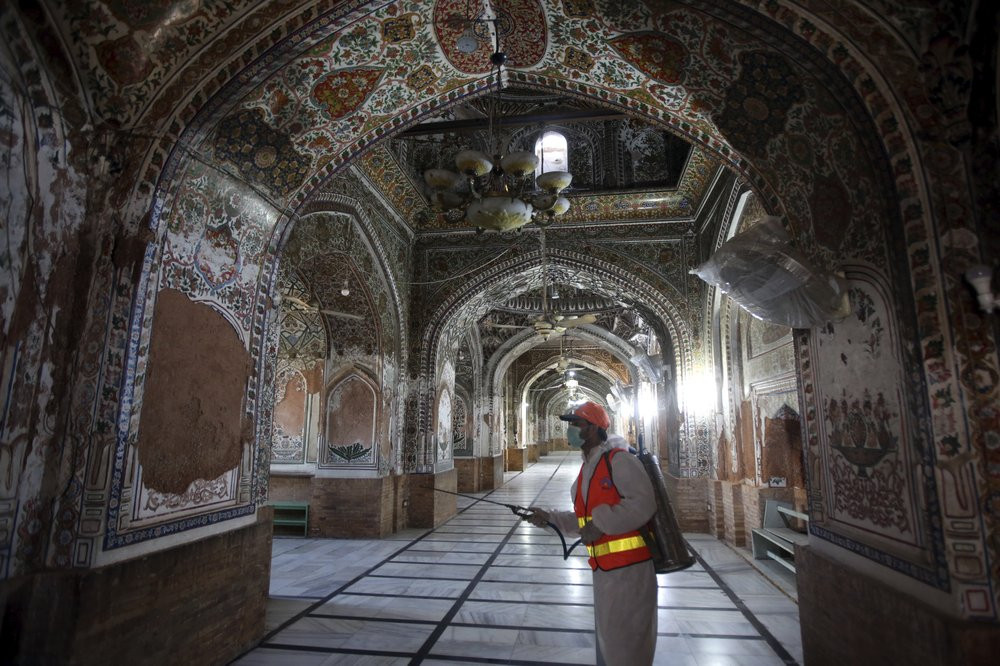 A worker disinfects a mosque for coronavirus, in Peshawar, Pakistan, Thursday, April 2, 2020. The government imposed a nationwide lockdown to try to contain the outbreak of the virus.