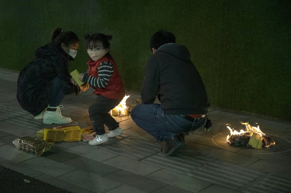 A family burn paper offerings for their departed relatives on the streets of Wuhan in central China's Hubei province on Saturday, April 4, 2020.