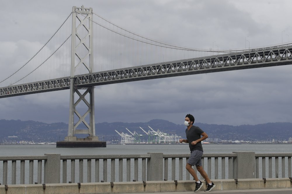 A man wears a mask to protect himself from the coronavirus while running in front of the San Francisco-Oakland Bay Bridge along the Embarcadero in San Francisco, Sunday, April 5, 2020.