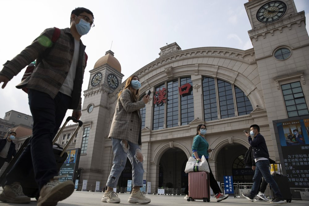 Travelers with their luggage walk past the Hankou railway station on the eve of its resuming outbound traffic in Wuhan in central China's Hubei province on Tuesday, April 7, 2020.