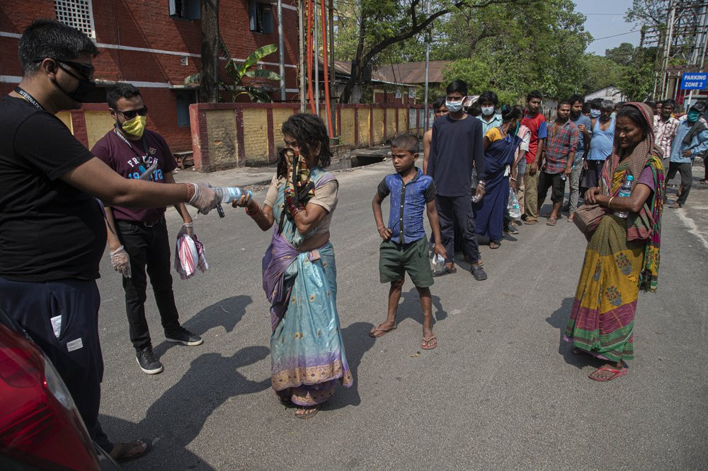 A group of Indians distribute free food and water to homeless people during a nationwide lockdown to curb the spread of new coronavirus in Gauhati, India, Sunday, April 19, 2020.
