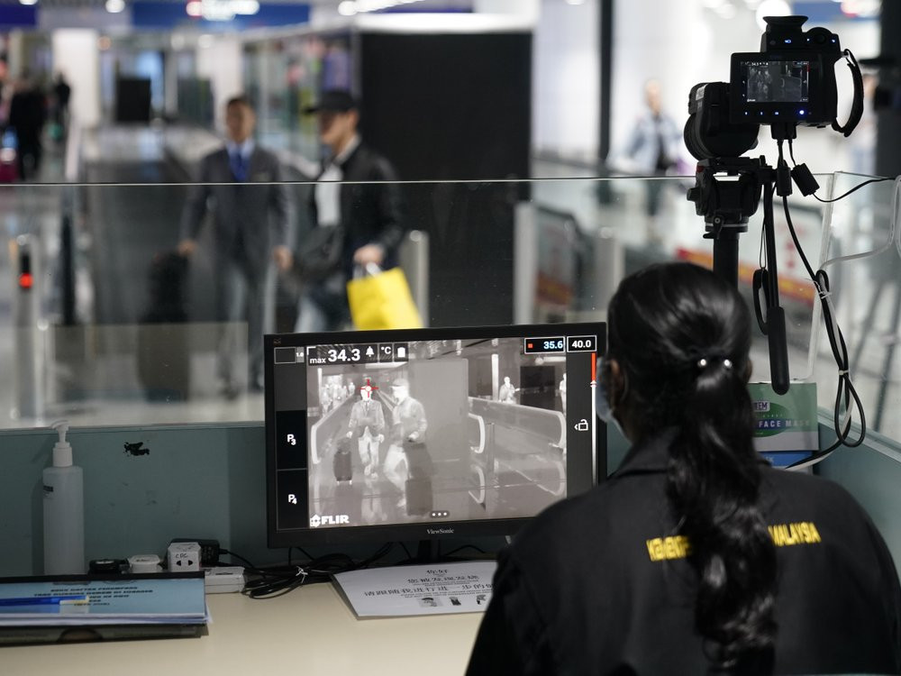 Health officials watch thermographic monitors at a quarantine inspection station at the Kuala Lumpur International Airport in Sepang, Malaysia, Tuesday, Jan. 21, 2020.