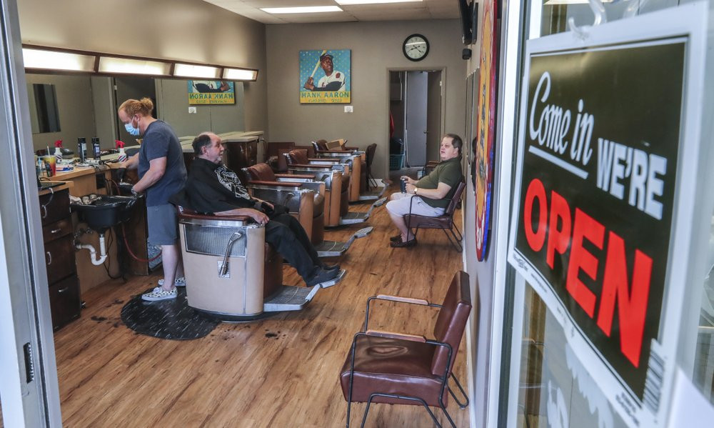 Barber and owner of Chris Edwards, left, wears a mask and cuts the hair of customer at Peachtree Battle Barber Shop in Atlanta on Friday, April 24, 2020.