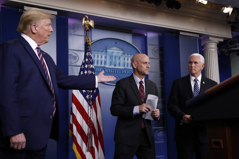 President Donald Trump gestures to Vice President Mike Pence as Stephen Hahn, commissioner of the U.S. Food and Drug Administration, steps back to the podium to answer a question during a briefing about the coronavirus in the White House.