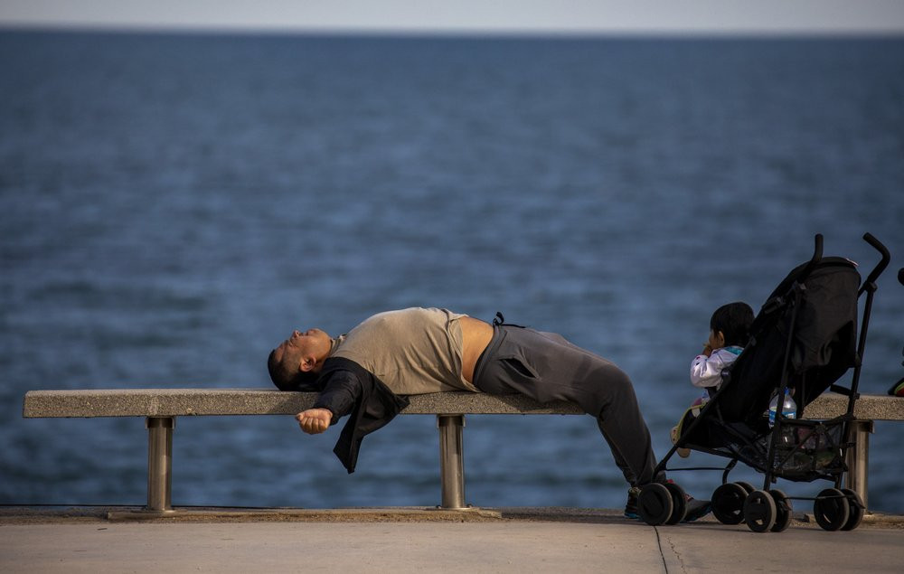 A man lies on a bench in front of the Mediterranean sea in Barcelona, Spain, Sunday, April 26, 2020 as the lockdown to combat the spread of coronavirus continues.