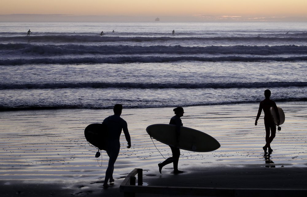 Surfers prepare to enter the water at Sumner Beach as level four COVID-19 restrictions are eased in Christchurch, New Zealand, Tuesday, April 28, 2020.