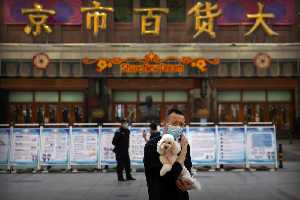 A man wearing a face mask to prevent the spread of the new coronavirus holds a dog as he stands along a pedestrian shopping street in Beijing, Tuesday, April 28, 2020.
