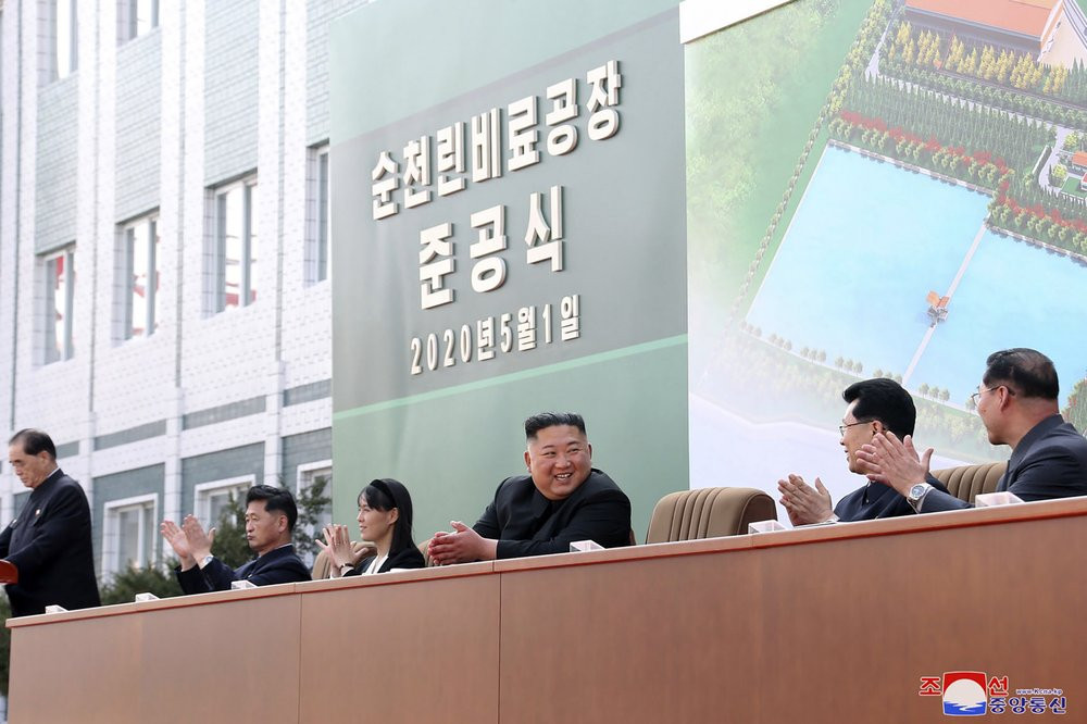 In this Friday, May 1, 2020, photo provided by the North Korean government, North Korean leader Kim Jong Un, center, claps during a ceremony at a fertilizer factory in South Pyongan, near Pyongyang, North Korea.