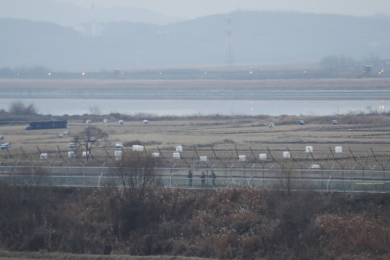 In this Dec. 16, 2019, file photo, South Korean army soldiers patrol along the barbed-wire fence in Paju, South Korea, near the border with North Korea.