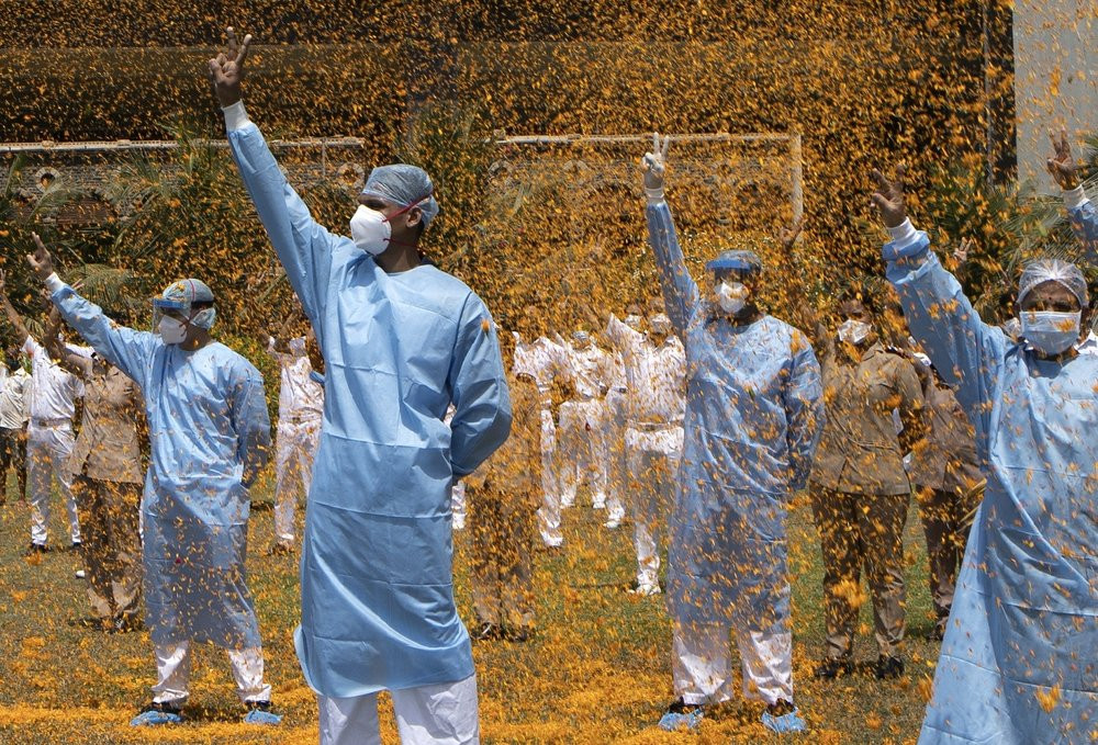 An Indian Air Force helicopter showers flower petals on the staff of INS Asvini hospital in Mumbai, India, Sunday, May 3, 2020.