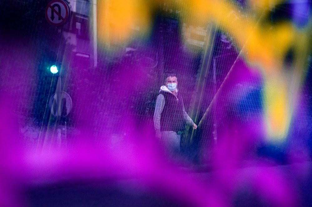 Seen through a bridge glass panel covered in graffiti a man wearing a face mask walks in Sarajevo, Bosnia, Wednesday, May 6, 2020.