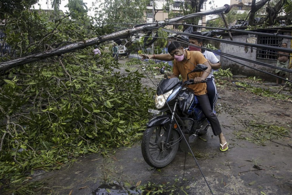 People make their way through damaged cables and a tree branch fallen in the middle of a road after Cyclone Amphan hit the region in Kolkata, India, Thursday, May 21, 2020.