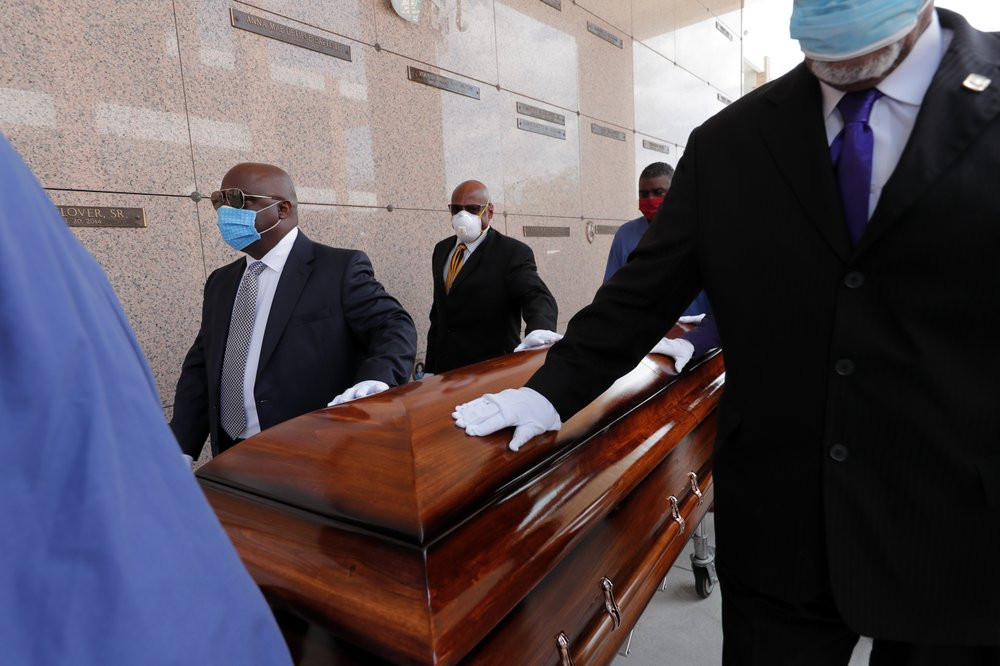 In this April 22, 2020, file photo, pallbearers, who were among only 10 allowed mourners, walk the casket for internment at the funeral for Larry Hammond, who died from the coronavirus, at Mount Olivet Cemetery in New Orleans.