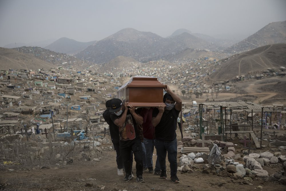 Relatives carry the coffin of a suspected COVID-19 victim at the Nueva Esperanza cemetery on the outskirts of Lima, Peru, Thursday, May 28, 2020.