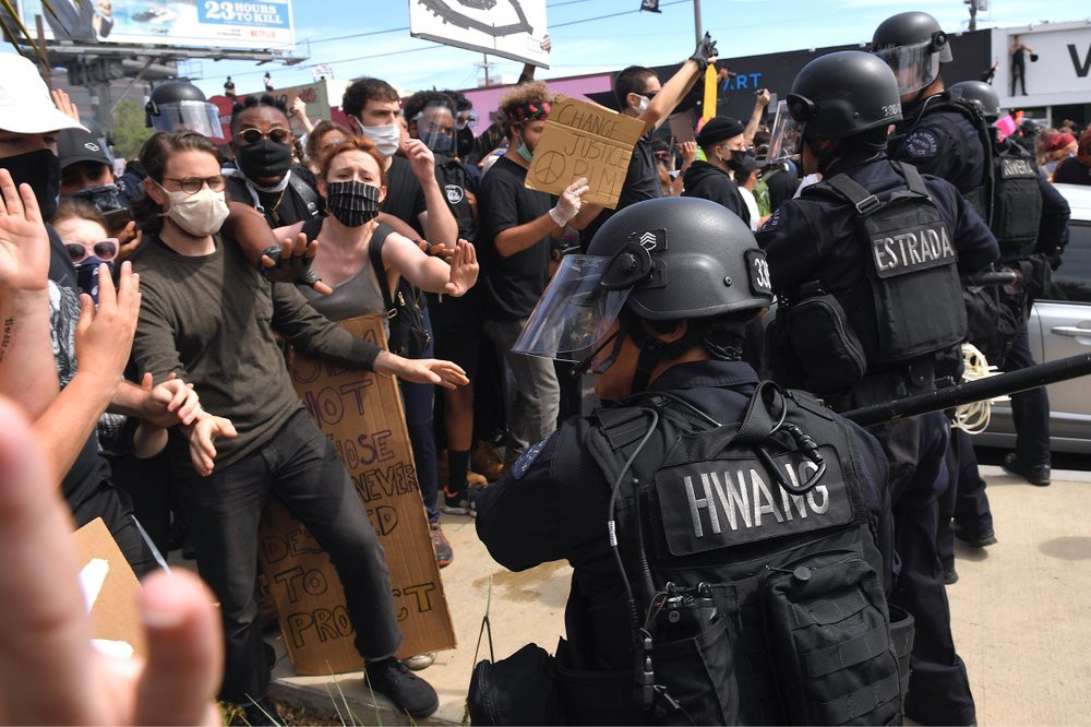 A Los Angeles police officer threatens protesters during a protest over the death of George Floyd Saturday, May 30, 2020, in Los Angeles.